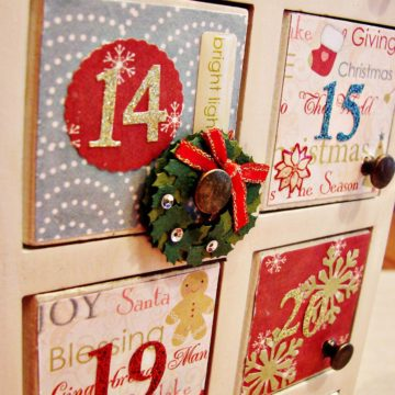 A wooden Advent calendar has been decorated with mod podge and craft paper.