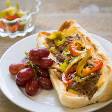 An open faced Italian Beef sandwich has pulled beef and strips of red and green peppers over the top. Sits on a plate next to a bunch of grapes.