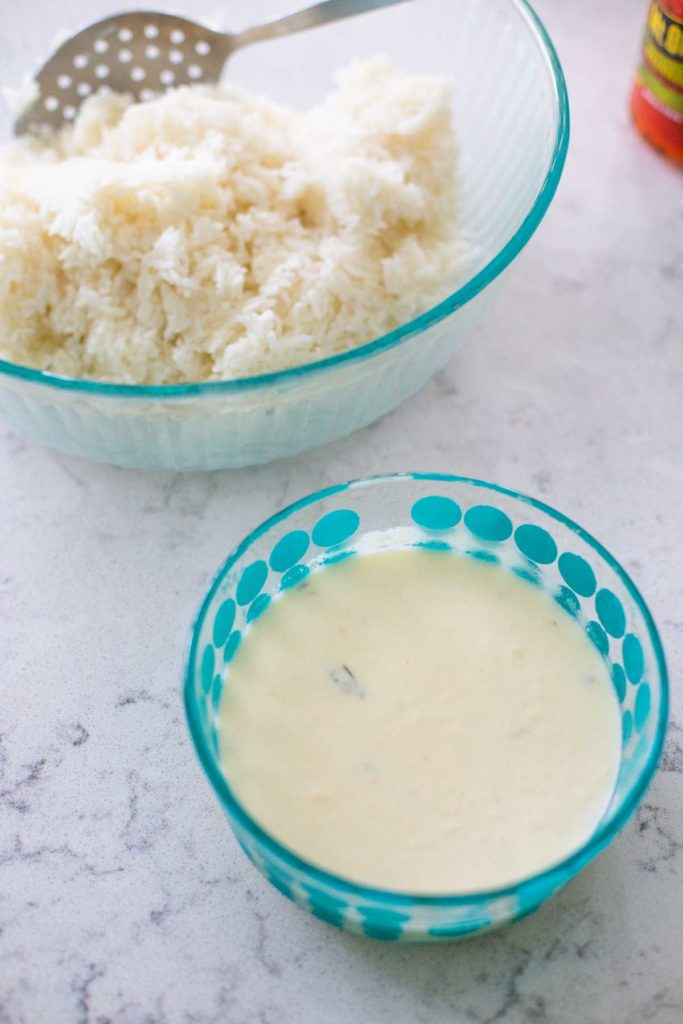 A bowl of homemade alfredo sauce is waiting by the rice.