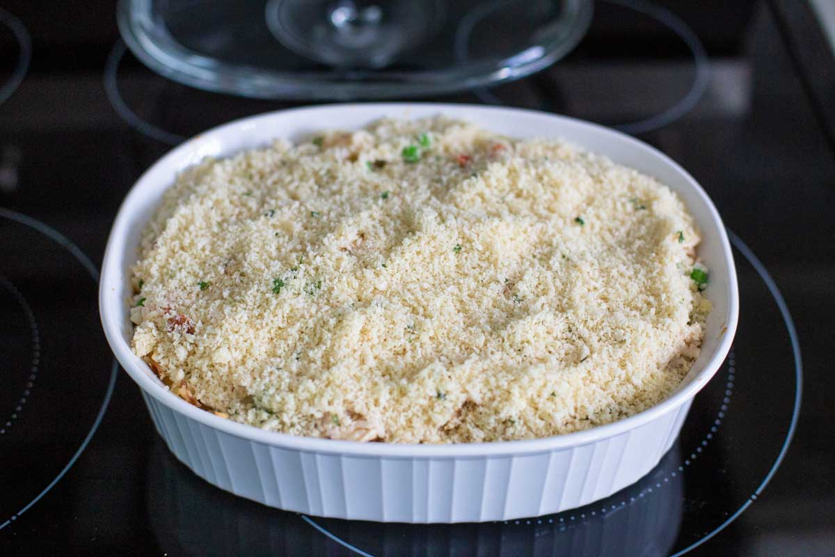 The chicken alfredo rice casserole sits on the stovetop and has had the breadcrumb topping sprinkled over the top to finish baking.