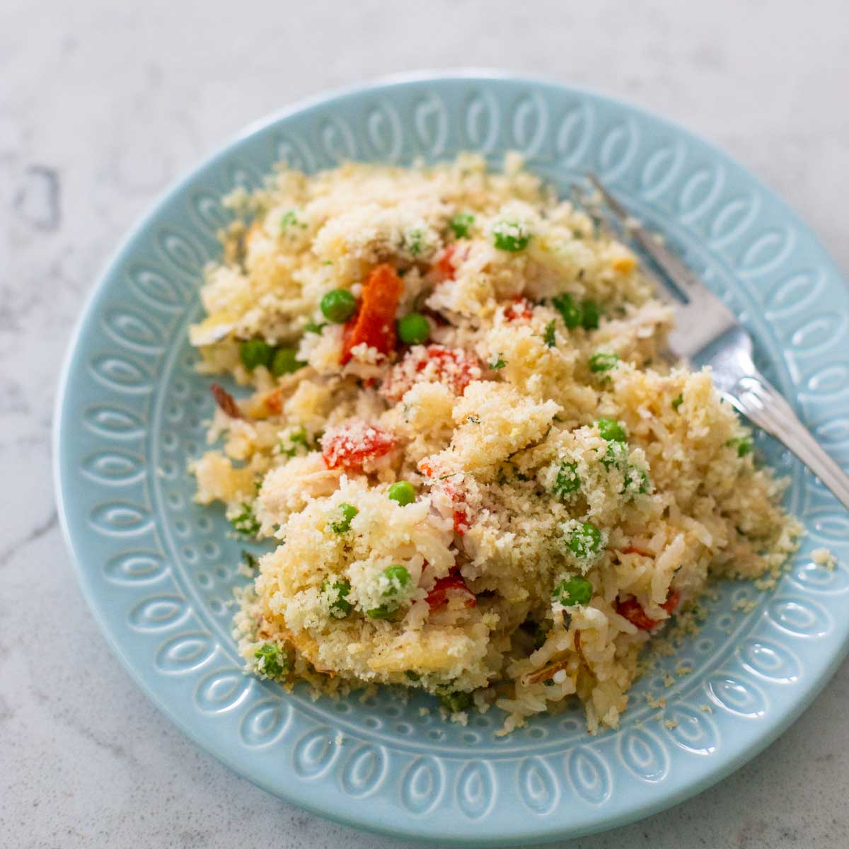 A blue plate has a serving of chicken rice alfredo casserole. You can see the red peppers and peas popping up through out the serving.