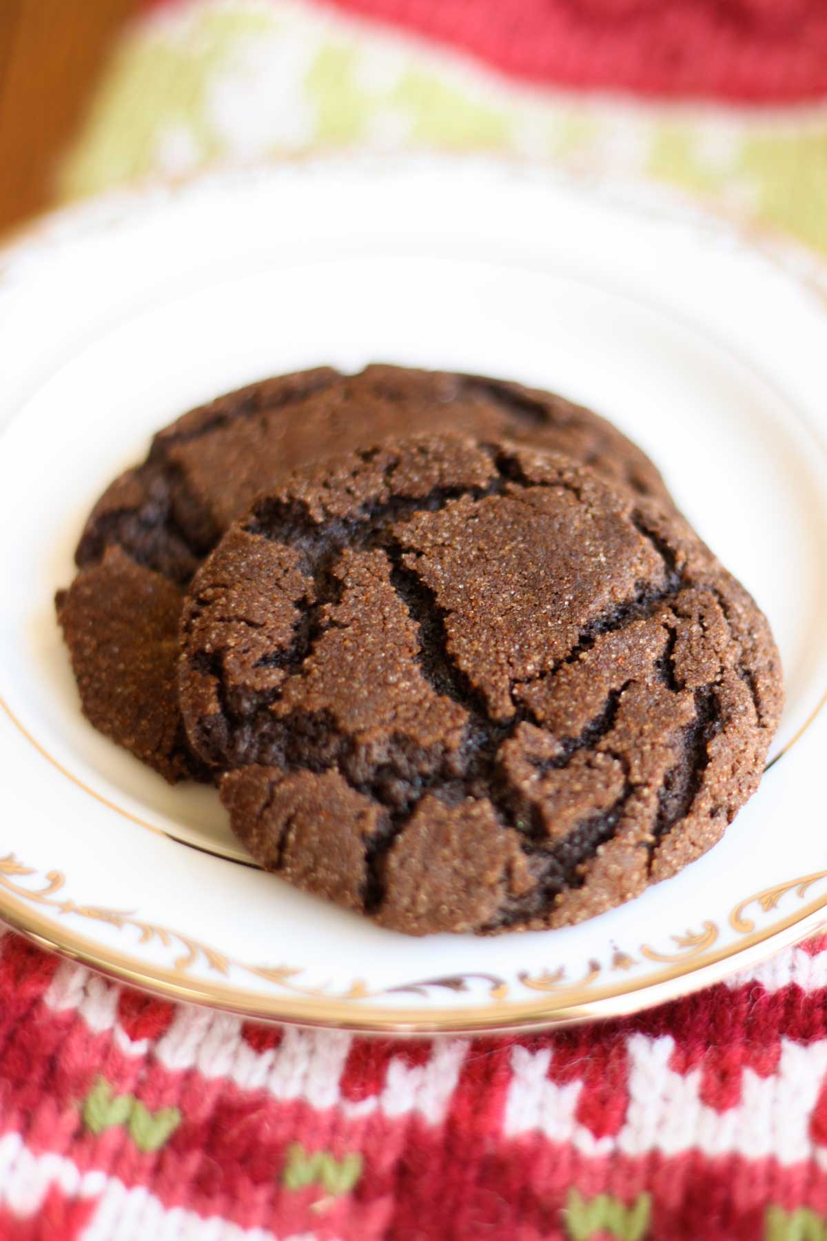 Two chocolate cookies with crinkles over the surface sit on a china plate. A knitted stocking sits under the plate.