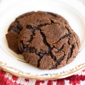 Two chocolate cookies sit on a china plate. The cookies have crinkles over the surface and are coated in a hot and spicy cayenne-cinnamon sugar coating.