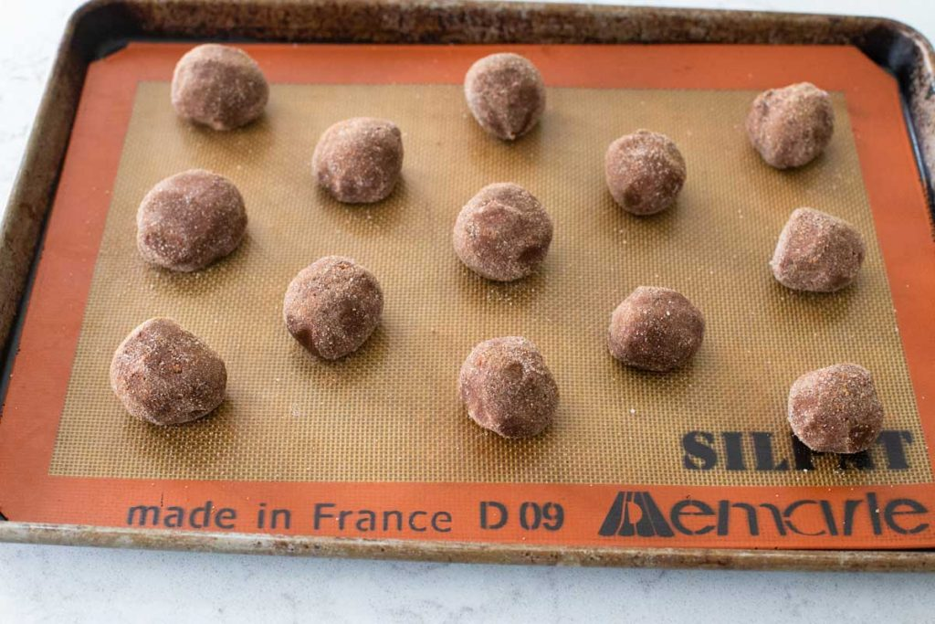 A cookie sheet is lined with a Silpat silicone mat and balls of cookie dough are lined up for baking.