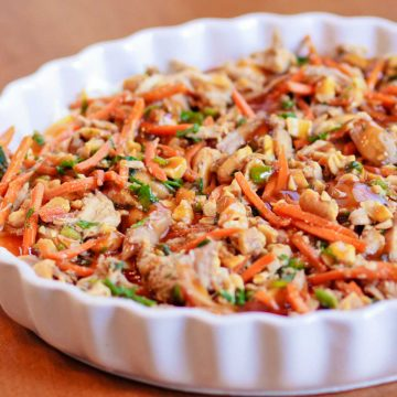 A ruffled pan holds oriental layer dip with shredded chicken, carrots, green onions, and cashews on a bed of cream cheese.