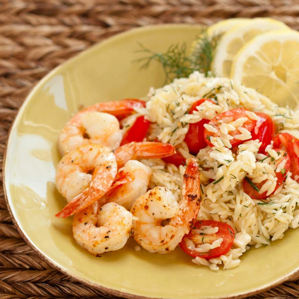 A plate of orzo pasta with fresh tomatoes sprinkled with fresh dill has roasted shrimp and lemon slices in the back.