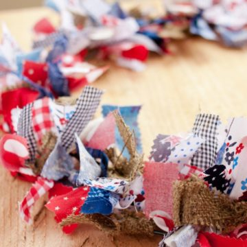 Red, white, and blue fabrics mixed with burlap to make a vintage looking rag wreath.