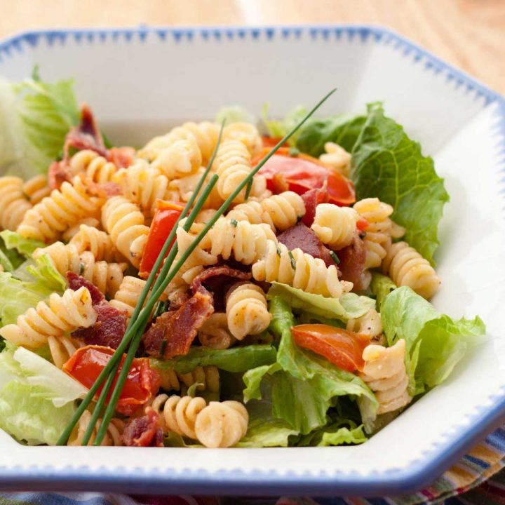 BLT pasta salad has corkscrew noodles, fresh lettuce, bacon, tomatoes, and fresh chives on top.