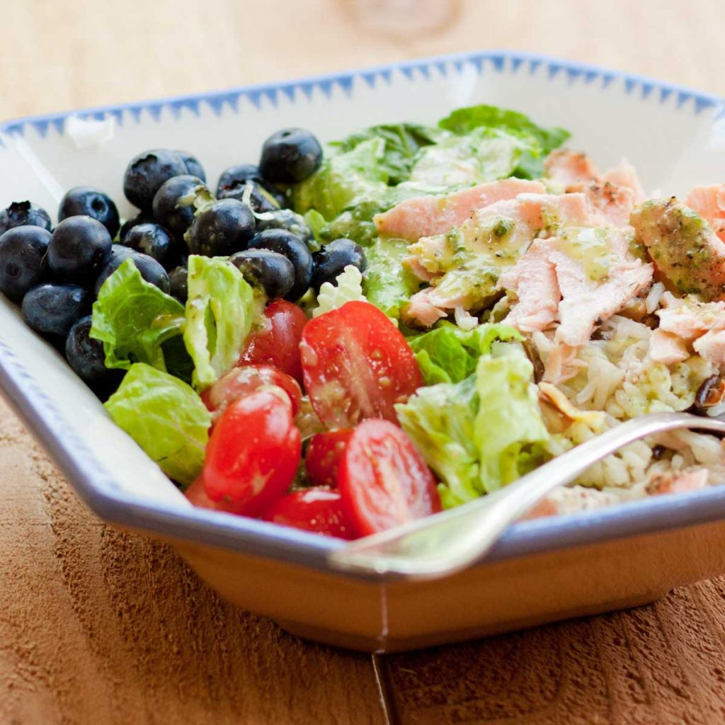 A big salad bowl shows the flaked leftover salmon, fresh blueberries, halved tomatoes, and green lettuce leaves.