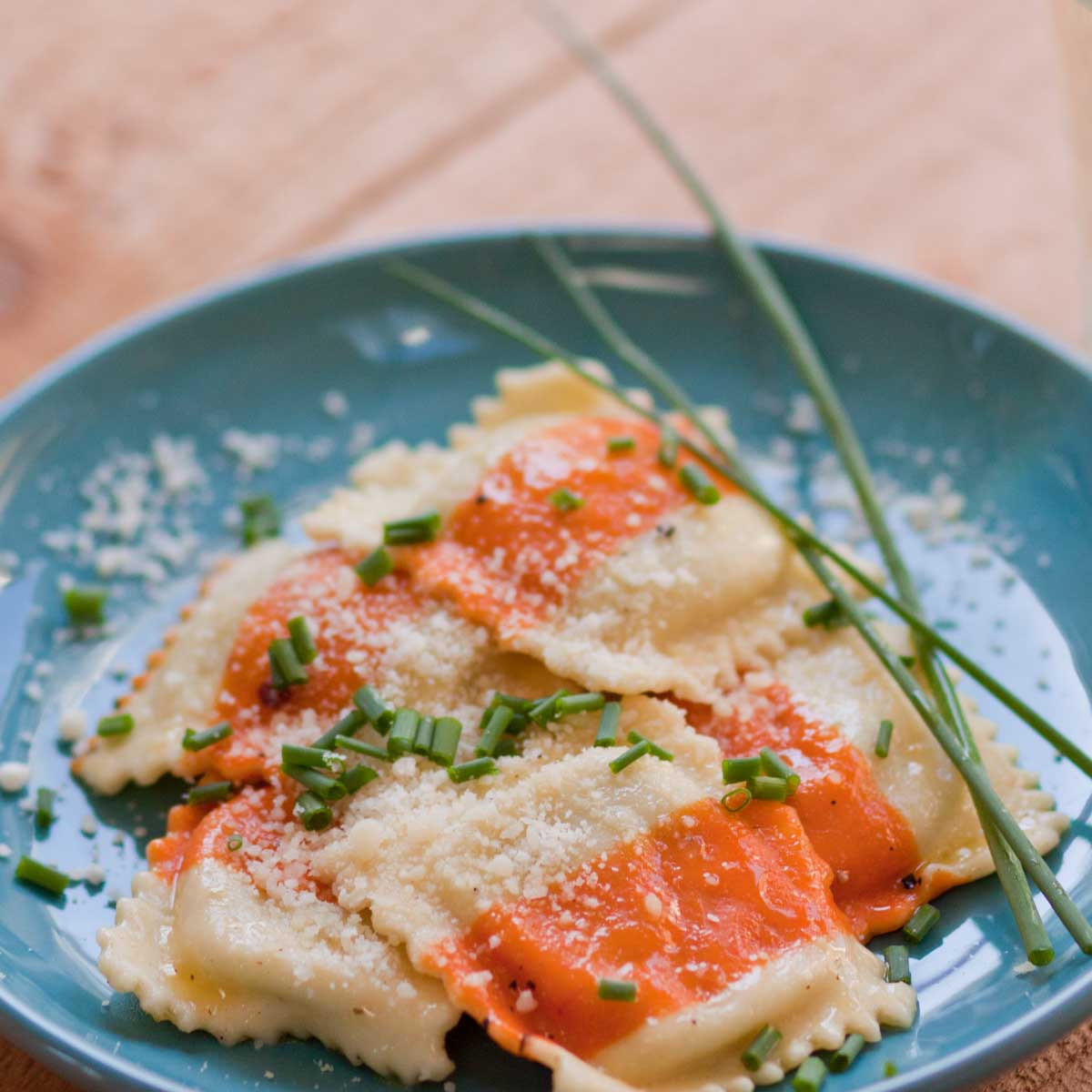 Striped ravioli are coated in a lemon butter sauce and sprinkled with minced fresh chives.