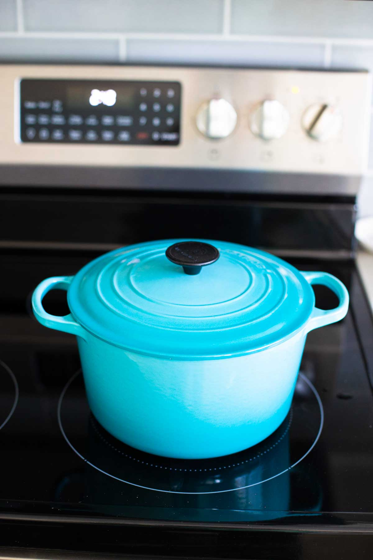 The blue dutch oven has the lid covering the stew cooking on the stove top.
