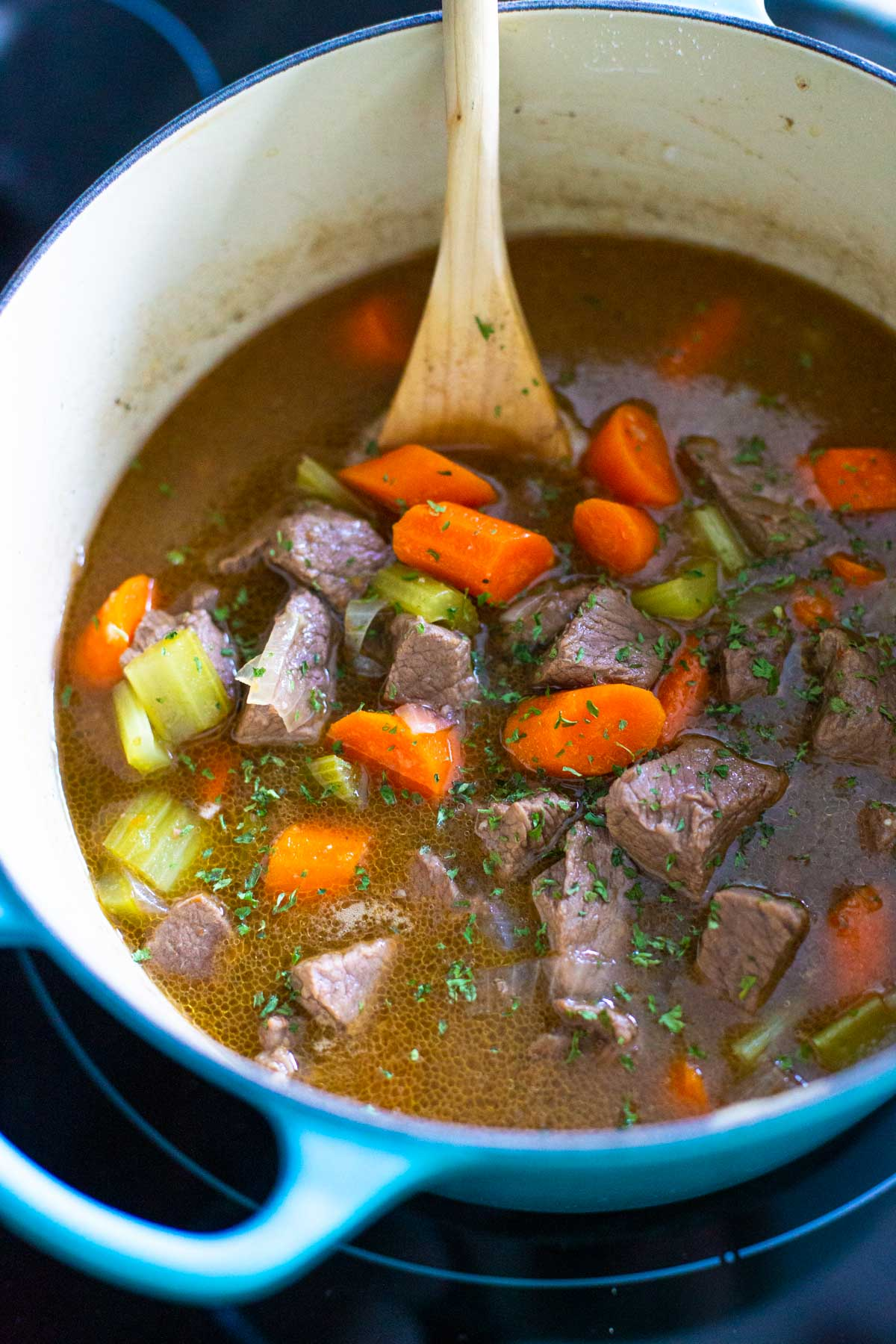 The finished beef stew sits in a dutch oven on the stove top.