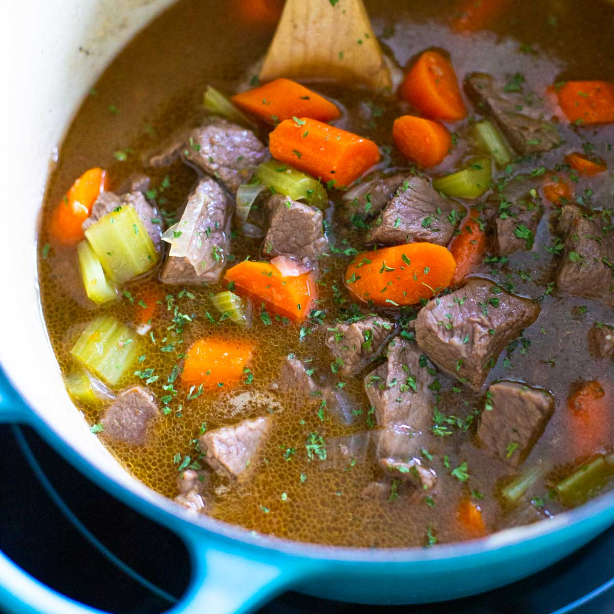 A blue dutch oven has a wooden spoon stirring beef stew.