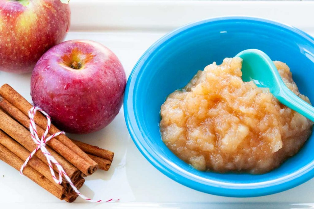A blue bowl of homemade applesauce sits next to a stack of cinnamon sticks wrapped in twine and two red apples.
