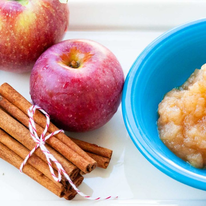 A stack of cinnamon sticks is wrapped with twine and sits next to two red apples. There's a bowl of applesauce to the side.