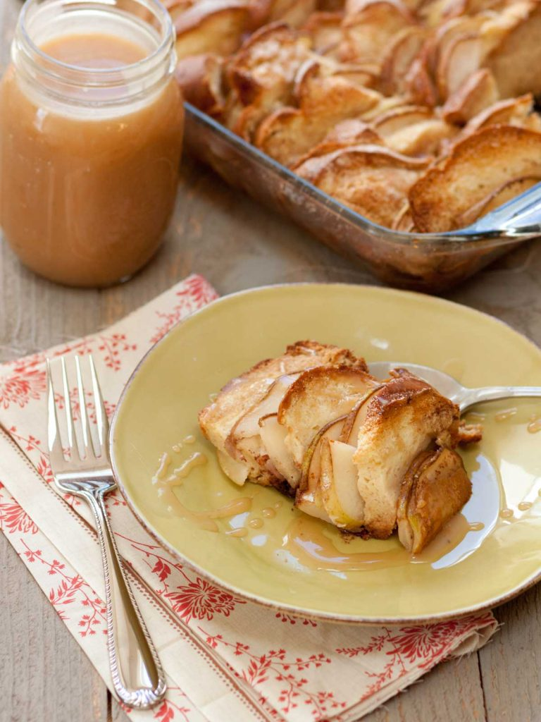 A serving of bread pudding with sliced pears sits on a plate. A jar of salted caramel sauce sits in the background next to the pan of bread pudding.