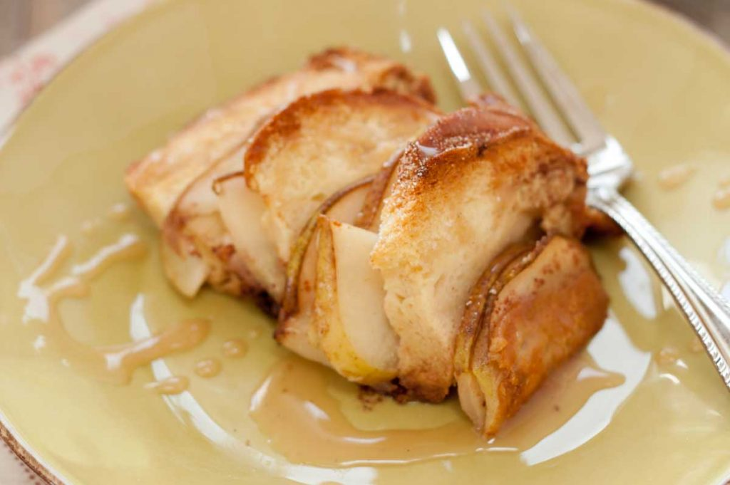 A close-up view of a serving of bread pudding with sliced pears and chocolate. There's a drizzle of caramel sauce over the top.