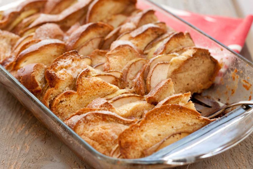 The full casserole pan of homemade bread pudding with pears and chocolate. The tops of each slice of bread are toasted a golden brown.