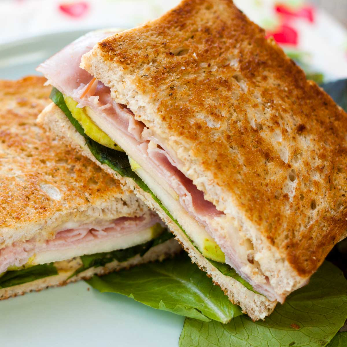 A grilled ham, pear, and havarti sandwich is cut in half so you can see the layers of filling inside.