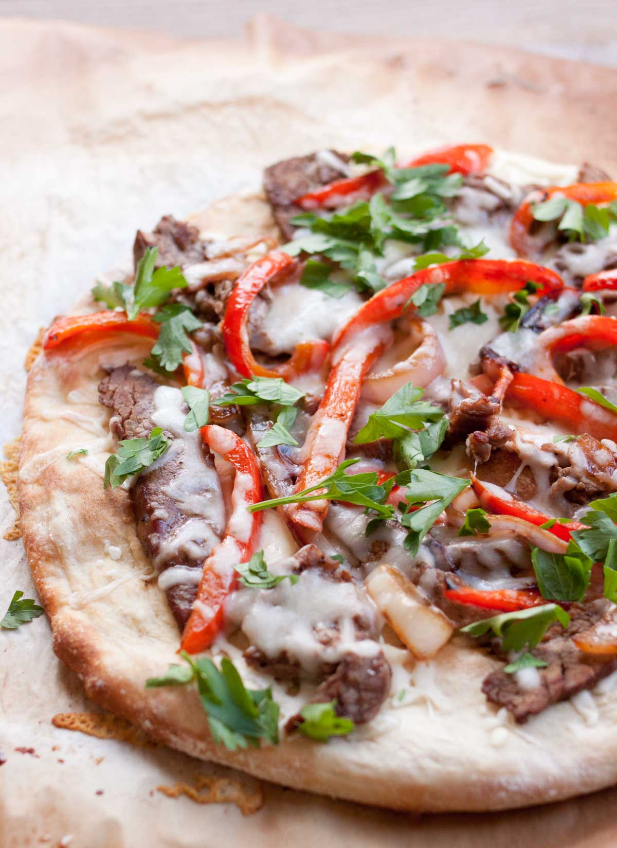 A flatbread pizza with strips of steak and red peppers is covered in melted cheese and fresh parsley.