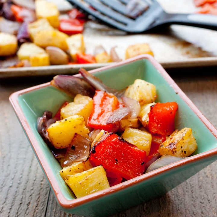 A serving bowl of roasted pineapple and pepper chunks sits in front of a roasting pan with spatula.