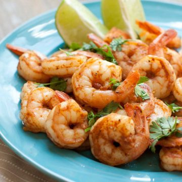 A blue plate has a pile of spicy shrimp with two lime wedges and a sprinkle of fresh cilantro over the top.