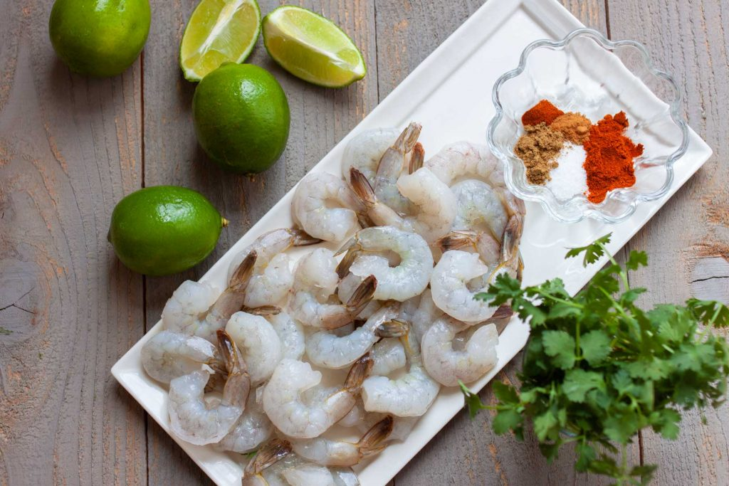 A platter of raw peeled and deveined shrimp next to a bowl of spices, a bunch of french cilantro, and several limes and lime wedges.