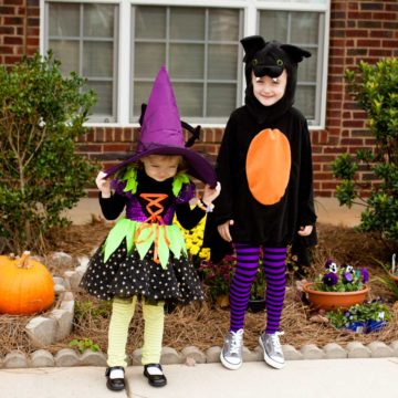 Two preschoolers in their Halloween costumes stand in front of their house.