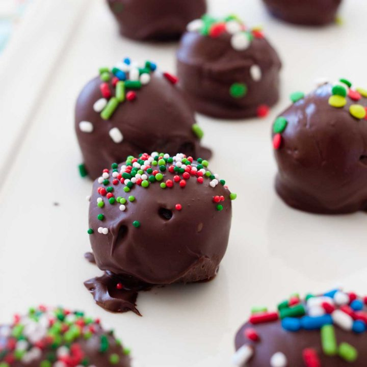 A tray of chocolate covered Oreo truffles with red and green sprinkles.