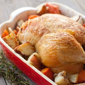 A golden brown roasted chicken sits on a bed of roasted potatoes and carrots in a red baking dish with a bunch of thyme on the side.