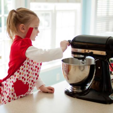 A little girl helps to operate the kitchen stand mixer while baking with parents.