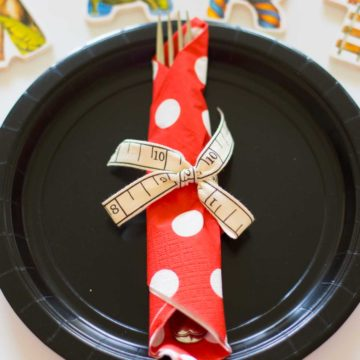 A black paper plate with utensils rolled up in a red and white polka dot napkin.