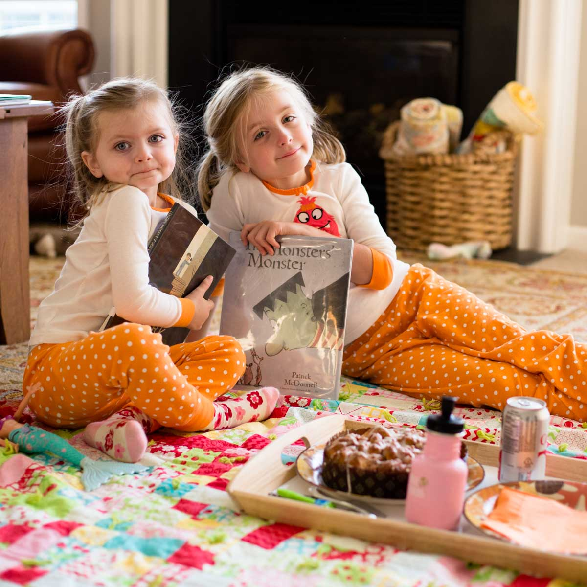 Two girls in Halloween jammies hold Halloween picture books and are sitting on the living room floor with breakfast treats.