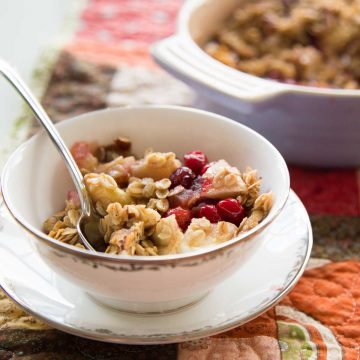 A china bowl has a serving of cranberry apple crisp with oat topping and a spoon.