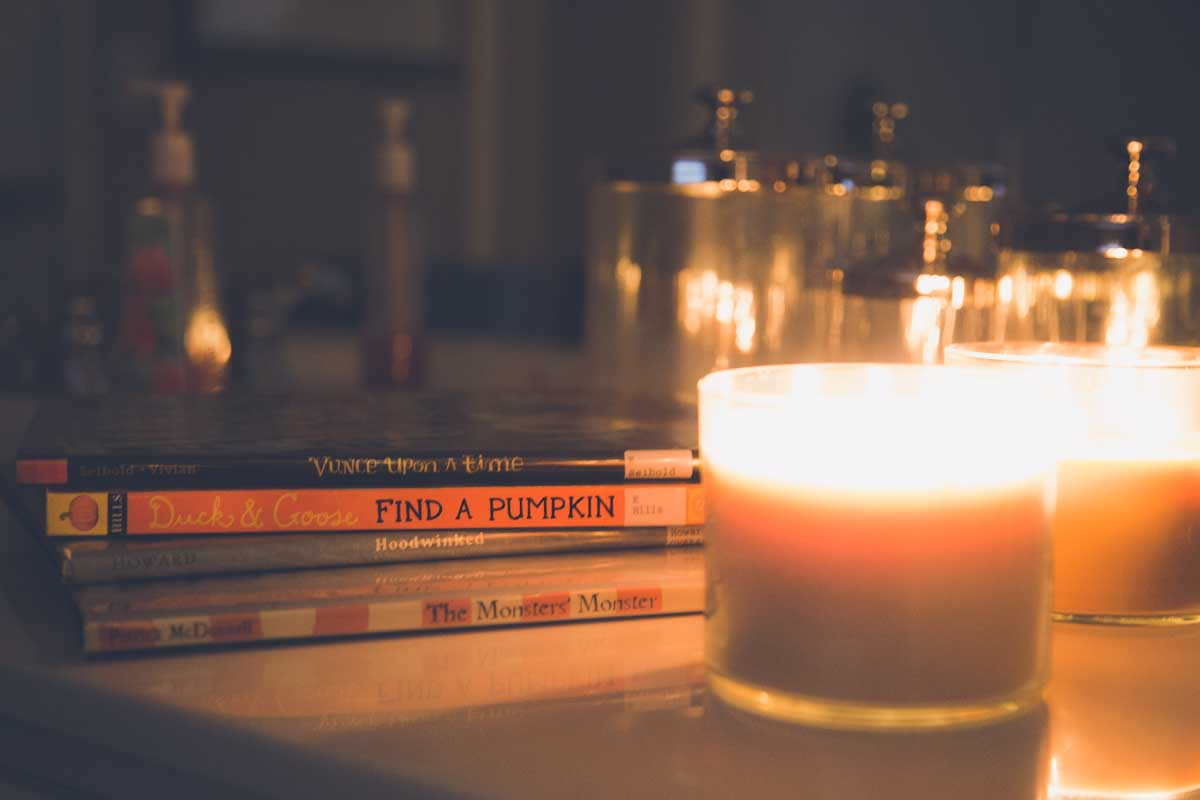 A stack of Halloween picture books sits on a bathroom counter next to a lit candle.