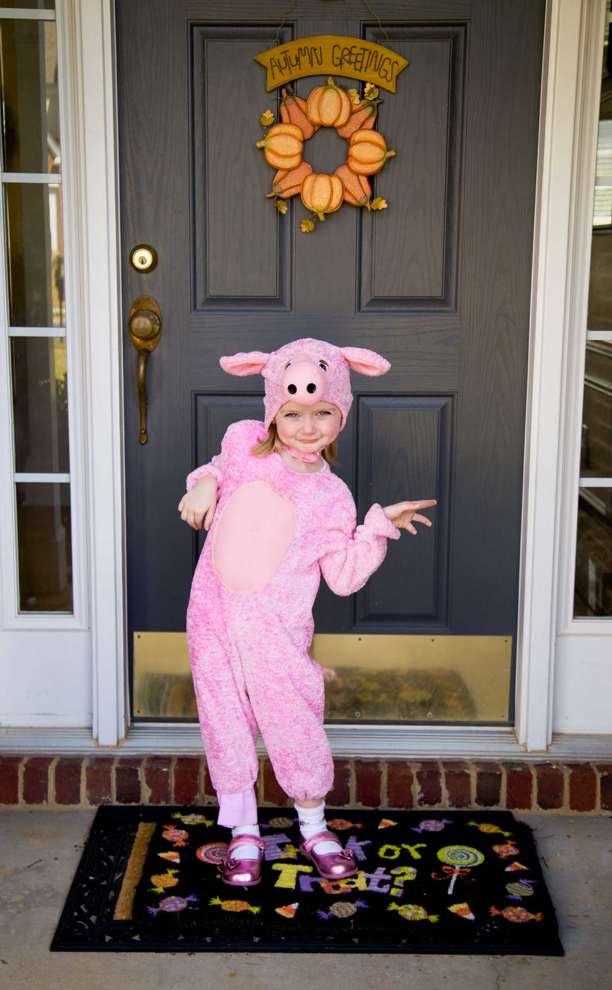 A little girl dressed in a farm day outfit stands in front of her front door.