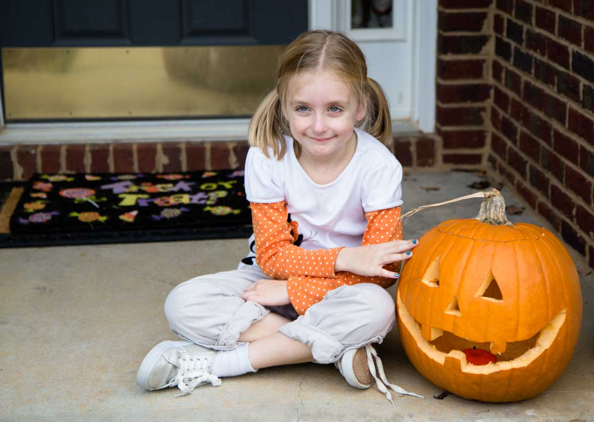 A young girl sits next to her carved pumpkin on the front step.