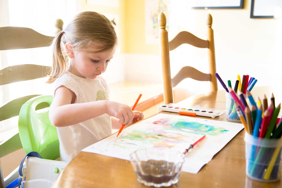A preschooler sits at a table working on a fall art activity.