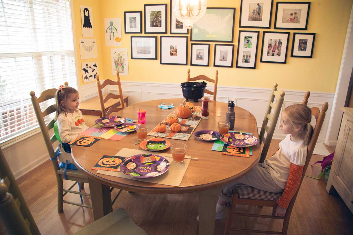 Two girls sit at a festive dinner table for Halloween.
