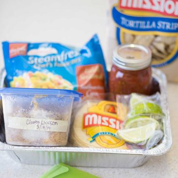 A meal train dinner kit featuring supplies for tacos sits in an aluminum tray for delivery.