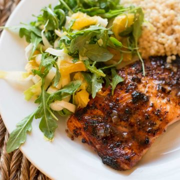 A plate with mustard glazed salmon and a leafy citrus salad with a scoop of couscous side dish.