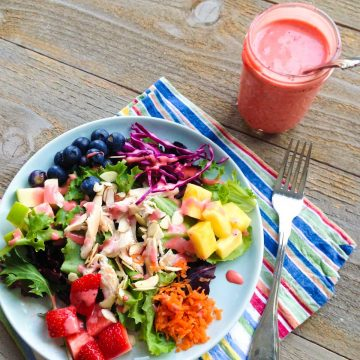 A jar of homemade strawberry vinaigrette sits next to a plate full of rainbow salad with fresh strawberries, carrots, pineapple, purple cabbage, blueberries, chicken, and lettuce.
