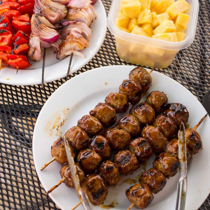 A platter of 4 meatball skewers with teriyaki glaze. A plate of grilled vegetables and fresh pineapple are in the back.