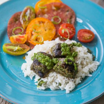 A blue plate holds a serving of rice with chunks of steak drizzled with fresh green chimichurri sauce. Fresh tomatoes are sliced in the back.