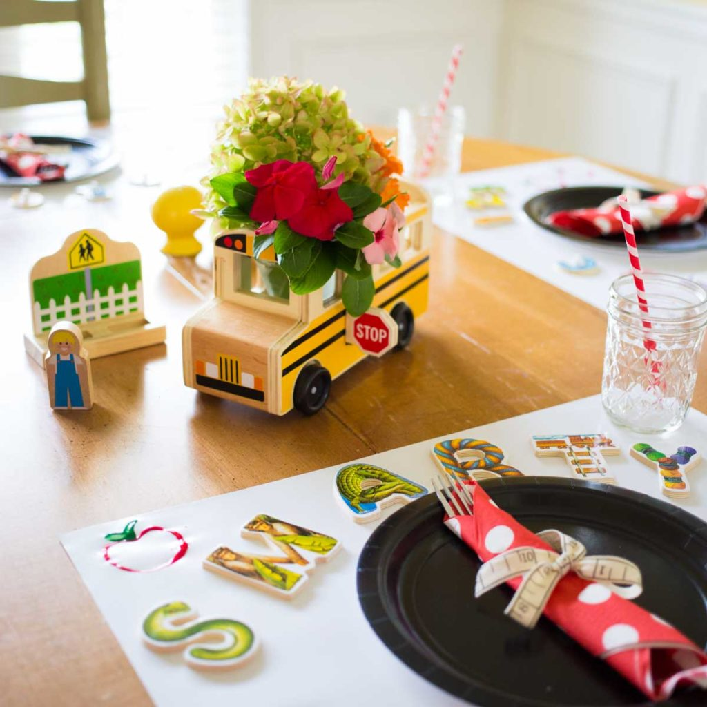 A table is set with a school bus floral centerpiece and cute ABC puzzle messages at each place setting.