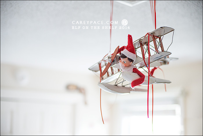 Elf on the Shelf flies airplane by Carey Pace