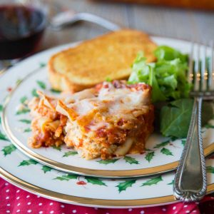 A slice of lasagna sits on a festive holiday plate with a green salad and slice of garlic bread.