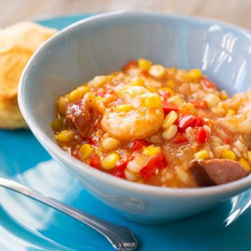 A blue bowl of spicy shrimp stew shows tons of corn, red peppers, spicy sausage, and big shrimp.