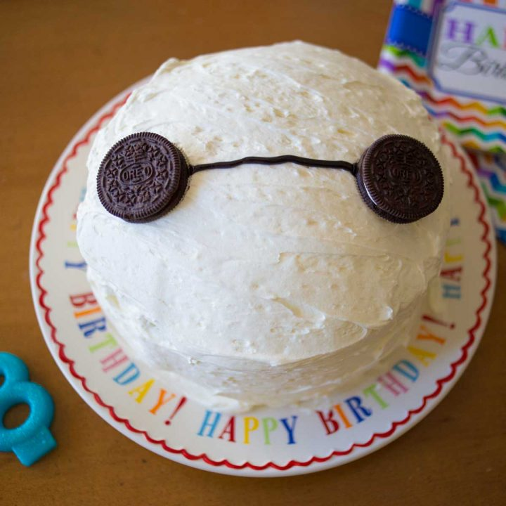 A round white-frosted layer cake has Oreo cookies for eyes to look like Baymax from Disney-Pixar's Big Hero 6.