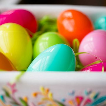 Colorful plastic Easter eggs in a lined basket.